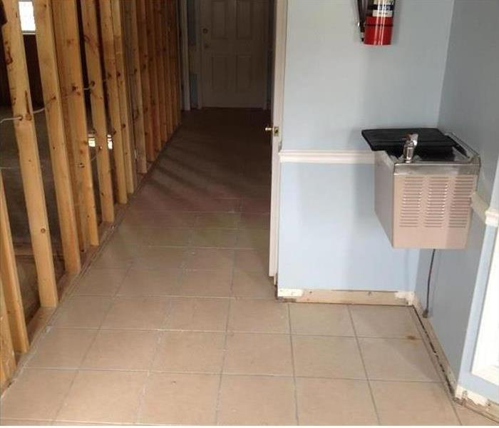 clean floor, studs showing where wall removed