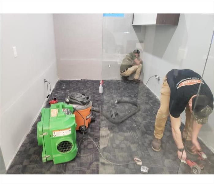 SERVPRO techs working on commercial water damage in shower