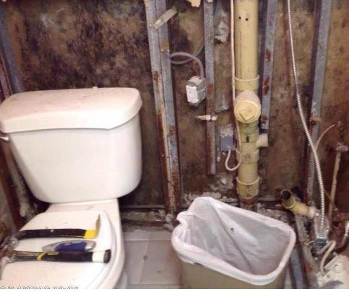 Bathroom with toilet and pipes in wall exposed