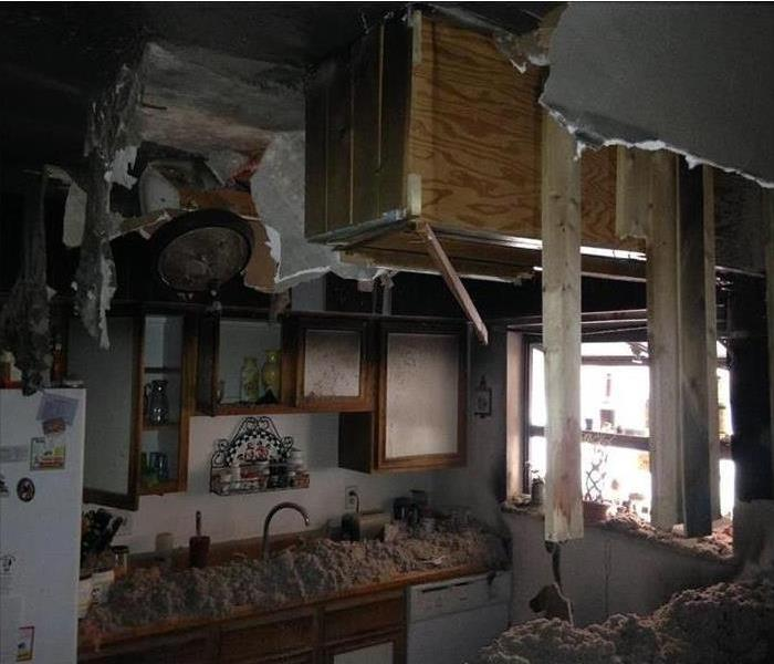 Kitchen with fire damage and debris