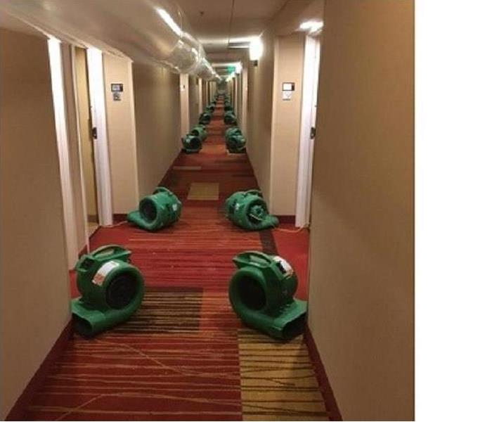 rows of air movers in hotel corridor, overhead ducting