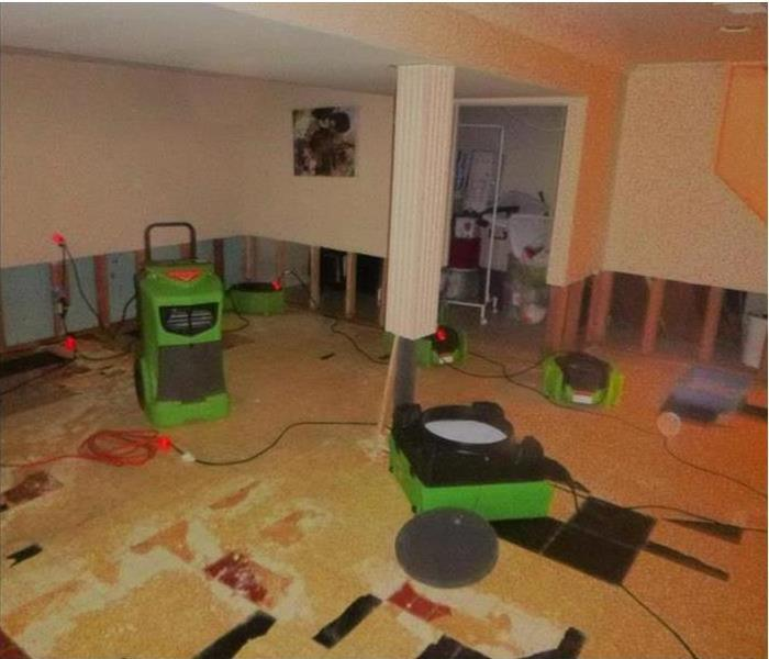 flood cuts on walls, green equipment drying basement that is finished