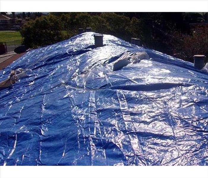 blue tarps covering a damaged roof
