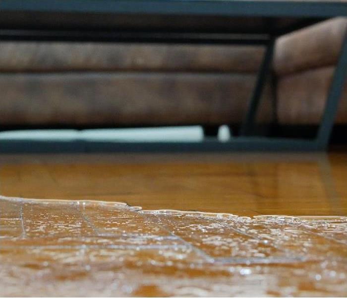 Close up of water flooding on living room parquet floor in a house